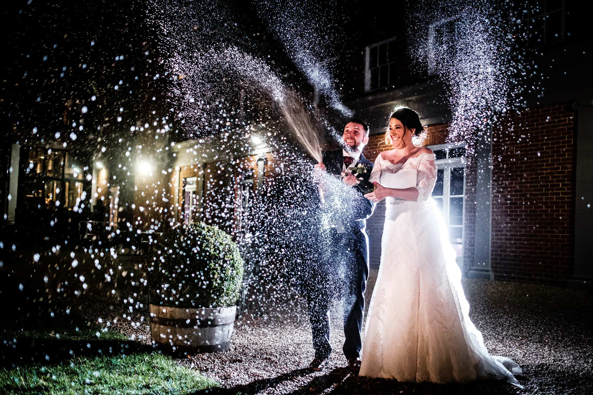 Bride and Groom spray champagne at their wedding at Highfield Park in Hampshire